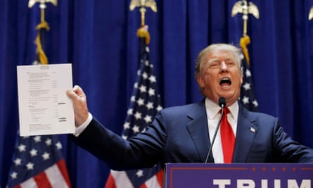 Donald Trump holds up his financial statement after declaring his candidacy for US president.