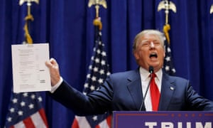 Donald Trump holds up his financial statement showing his net worth as he formally announces his campaign for the 2016 Republican presidential nomination at Trump Tower in New York on 16 June 2015.