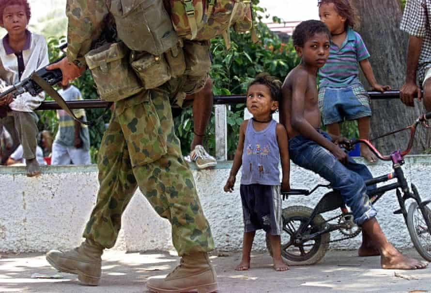 An Australian soldier on a foot patrol walks past East Timorese children in Dili in September 1999.