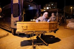 Jerusalem, Israel. Ultra-Orthodox Jews of the Kadisha Jewish burial organisation (Hevra kadishah) with the coffin of 72-year-old Rabbi Masoud Hamu of France, who died from Covid-19