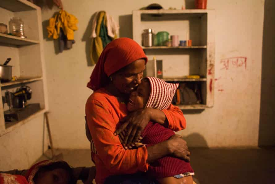 Saeeda hugs and kisses her 5 years old daughter in their home in Mewat District, Haryana, India