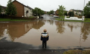 A child stands at the edge of a flooded road in the Twinbrook estate in Lisburn Northern Ireland.