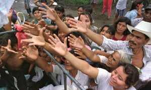 People in San Carlos, El Salvador, reach out for aid in the aftermath of Hurricane Mitch in 1998.