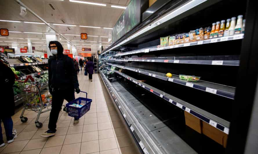 People shop in aisles with empty shelves in a Sainsbury's supermarket in east London in March