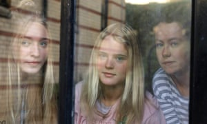 Three students pictured through a window