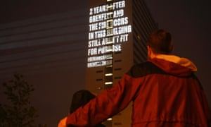 """A message projected onto a building, reading """"2 years after Grenfell and the fire doors in this building still aren't fit for purpose #demandchange Grenfell United"""""""