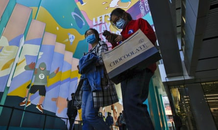 Shoppers wear face masks in Beijing. RT-Mart has apologised for the signs on clothing marking large sizes as 'horrible'.