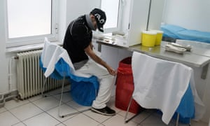 A drug user cleans his arm at a supervised injection site in central Athens.
