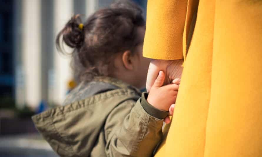 Small child holding mother's hand.