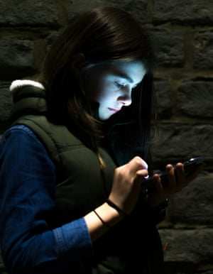 Girl using her phone outdoors at night. A young teenager's face is lit up by the screen of her phone.