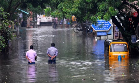People walk along flooded roads in southern India