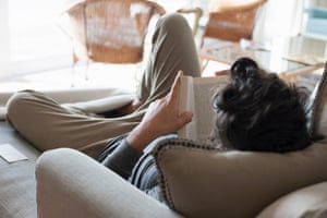 Mid adult man relaxing on sofa, reading book, rear view