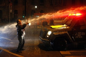 Santiago, Chile A demonstrator is hit by a police water cannon during a demonstration demanding an end to the private retirement pension