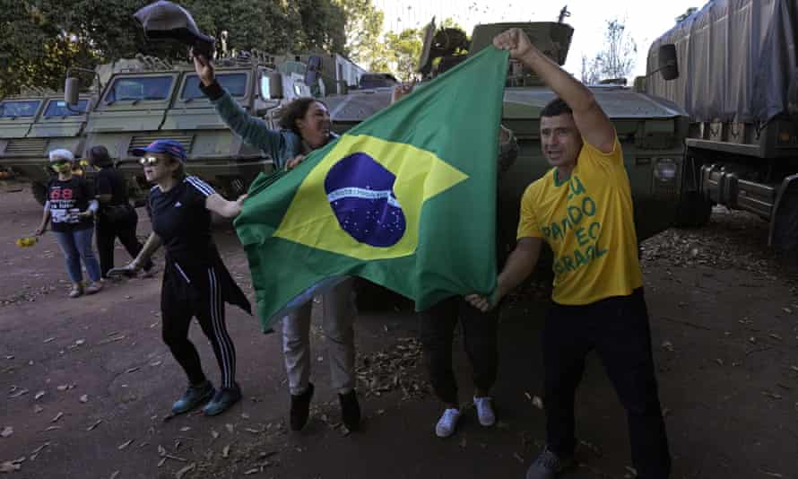 Supporters of Jair Bolsonaro cheer with a Brazilian flag as protesters hold flowers to give to soldiers from the military convoy in Brasilia