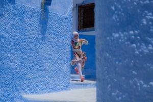 A young girl running in full flight in striking pale blue medina of Chefchaouen, Morocco