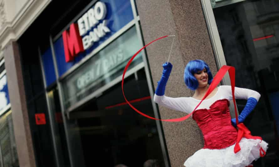 A street performer stands outside Metro Bank