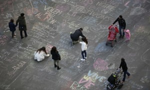 People write messages on the ground at Place de la Bourse, a square outside the Brussels stock exchange.