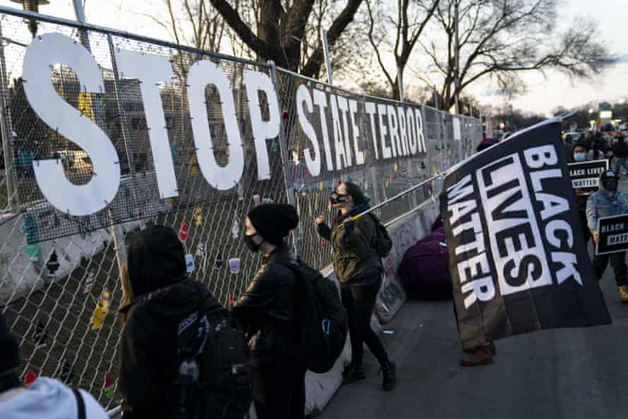 A sign reading 'stop state terror' hangs on a perimeter security fence as protests over the fatal shooting of Daunte Wright by a police officer continued on Saturday.