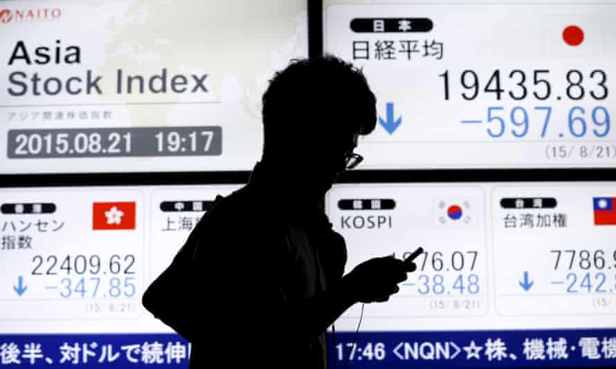 An electronic board displaying various Asian stock market indices outside a brokerage in Tokyo