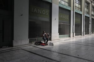 A street musician plays the accordion in an arcade where shops are closed down in central Athens due to the recession. The European Central Bank provided more liquidity to Greece's banking sector, after the bailout deal was approved.