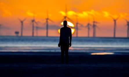 The sun sets behind Burbo Bank wind farm and Another Place at Crosby beach, Merseyside.