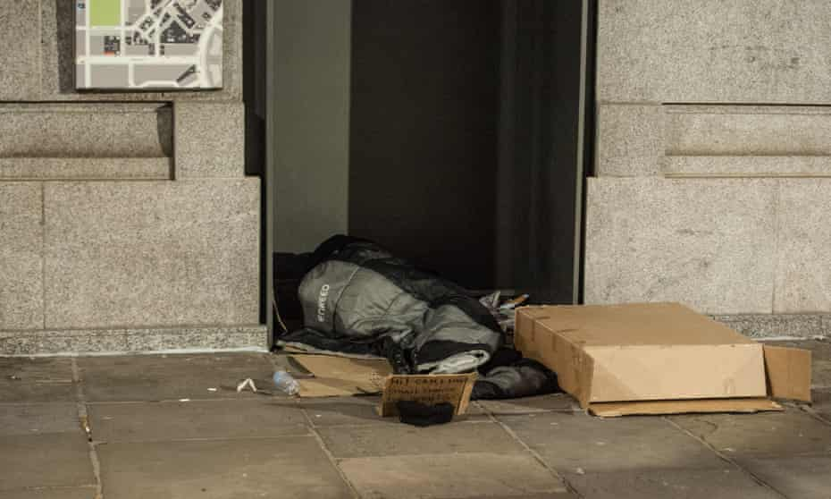 homeless person lying down in a doorway