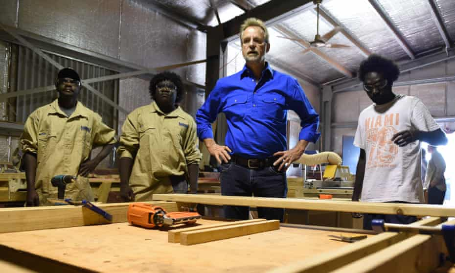 white man stands next to young Indigenous men in a workshop