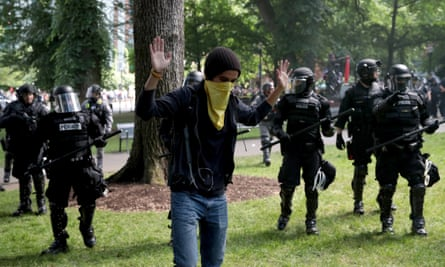 A man raises his hands as police clash with demonstrators as they try to clear 'Antifa' members and anti-Trump protesters on 4 June 2017 in Portland, Oregon.