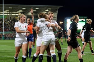 England's wing Lydia Thompson celebrates with team-mates after scoring a try.