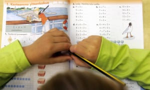 A child studying his school book in a primary school in Finland