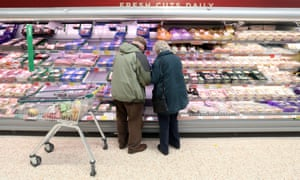 Shoppers looking at meat packing in supermarket