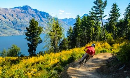 Downhill mountain biking at Queenstown Bike Park South Island New Zealand Cecil Peak and Lake Wakatipu behind.