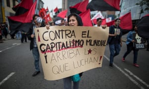 A demonstrator in Lima against the IMF and World Bank meetings holds a banner that says: 'Against world capitalism. Long live those who fight.'