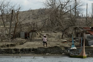 A woman stands near damaged houses