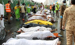 Saudi emergency personnel stand near bodies of hajj pilgrims