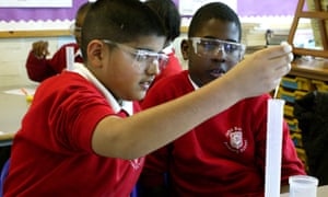 Pupils wearing safety glasses conduct an experiment