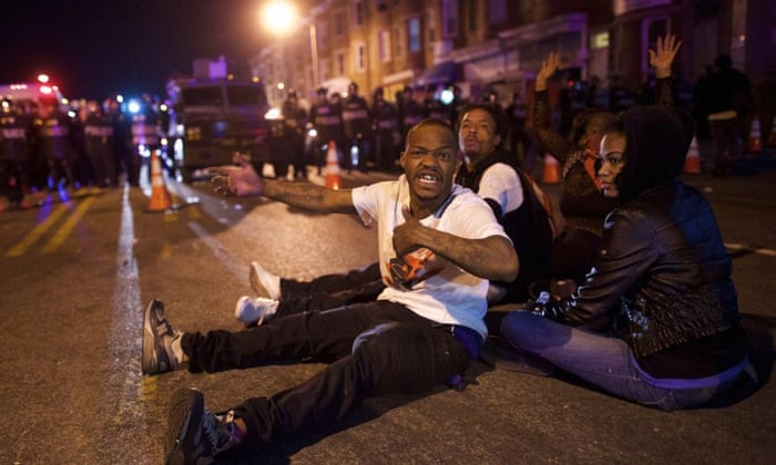 Protesters defy the 10pm curfew in front of police officers the night after citywide riots over the death of Freddie Gray.