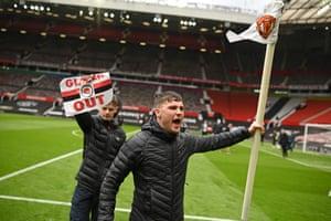 One person holds a corner flag aloft inside Old Trafford.