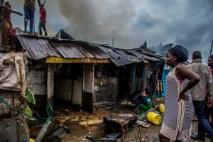 A woman watches as young men try to extinguish a blaze that destroyed her entire business. Domestic fires are common in Kibera where cooking fires and small stoves are used inside wooden shacks.