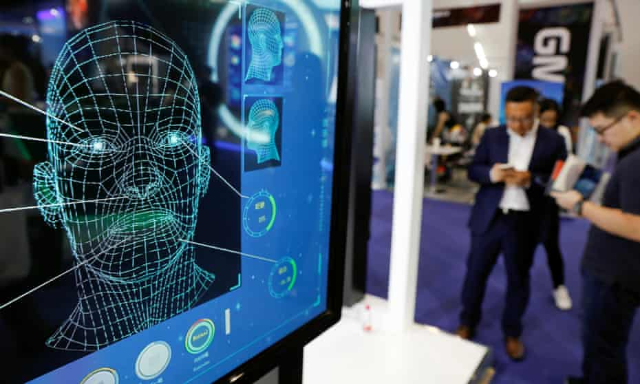 Visitors check their phones behind the screen advertising facial recognition software during Global Mobile Internet Conference (GMIC) .