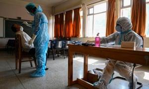 Seorang pekerja medis mengumpulkan sampel usap dari anggota staf di dalam ruang kelas di Srinagar, India.