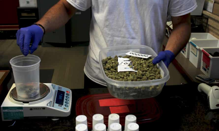 A worker at a medical marijuana dispensary in the Boston suburb of Brookline weighs cannabis.