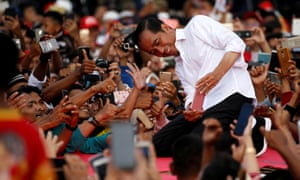 Joko Widodo takes pictures with his supporters during his first campaign rally at a stadium in Serang, Banten province in Indonesia