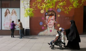 Muslim mother and children pass mural of local Brixton hero David Bowie