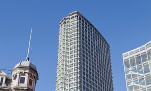 The top third of Centre Point tower block against a blue sky