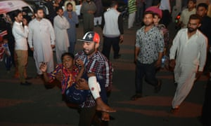 A man carries an injured child to the hospital in Lahore after the bombing.