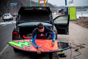 A surfer waxes his board at La Pampilla beach, in Lima