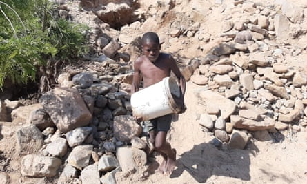 A boy carries a bucket full of river sand