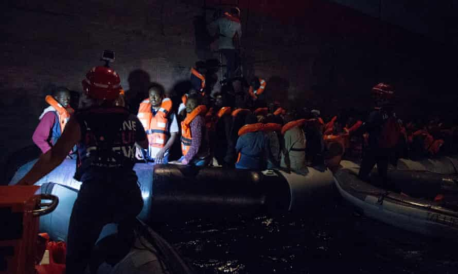 Migrants boarding a container ship of Danish shipping company Maersk Line after they were rescued from a shipwrecked vessel at sea. June 2018.
