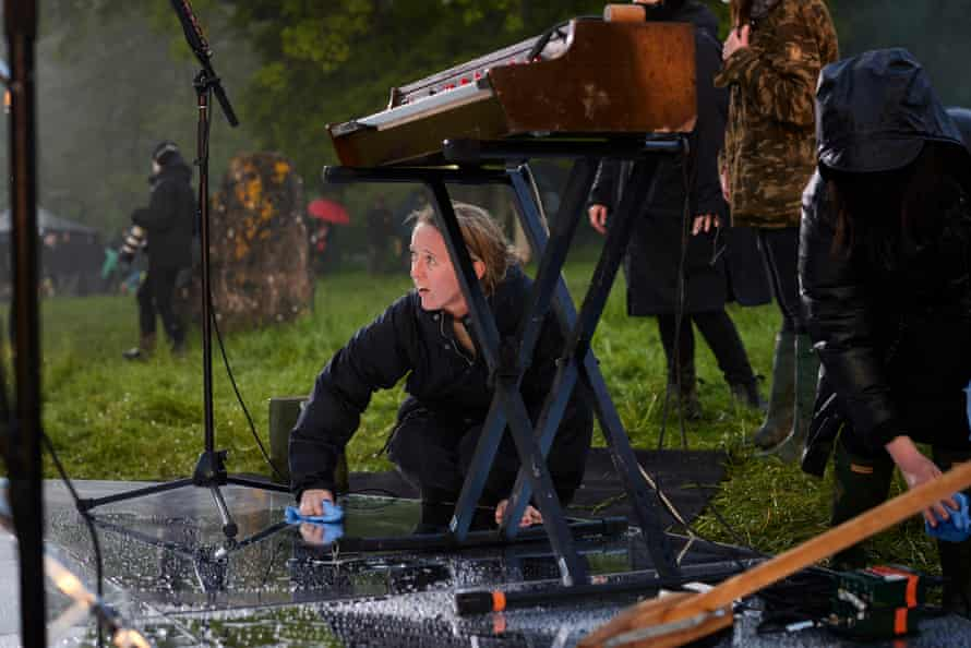 Emily Eavis helps to dry the stage after rainfall at the Stone Circle, before Haim start their performance.